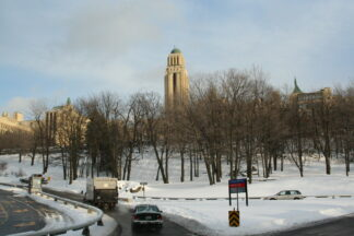 the university of Montreal's tower rises above leaf-bare parkland trees in a snow-clad scene