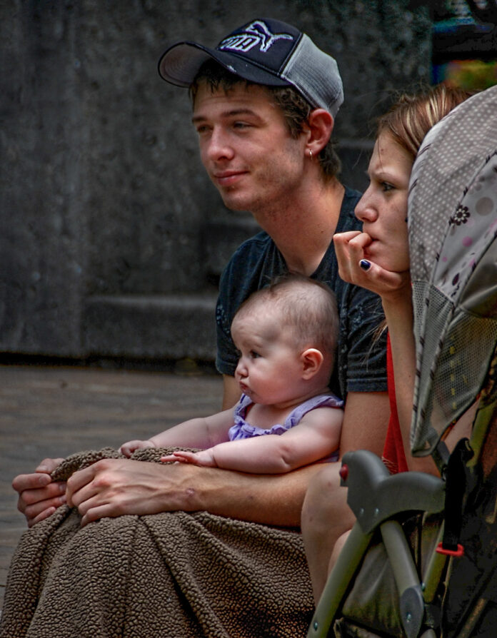 A pair of pensive young people set with their baby