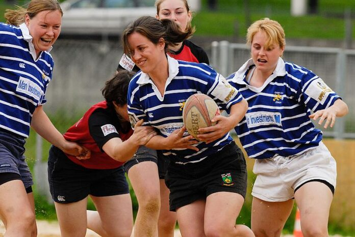 a group of young women in striped shirts fight for a rugby ball