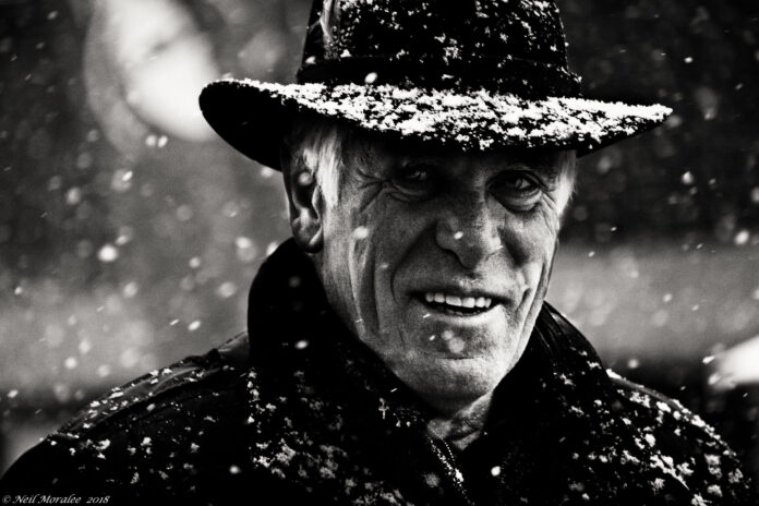 Closeup of a weathered face under a black hat flecked with white snowlflakes.