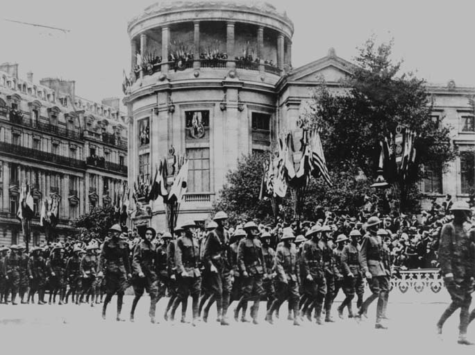 A black and white photo of U.S Marine Corps troops marching past Paris Buildings