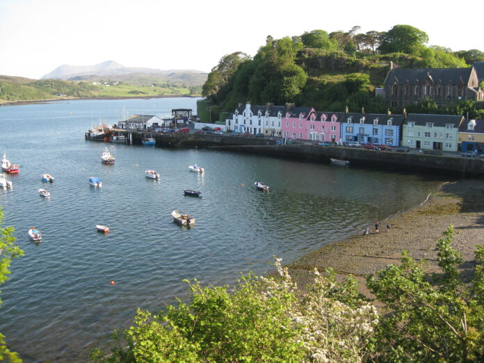 Portree harbour lined with painted houses in front of a sea of moored boats