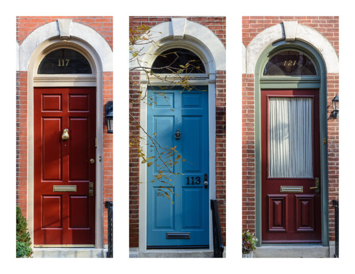 three colourful doors lined up in the side of a building