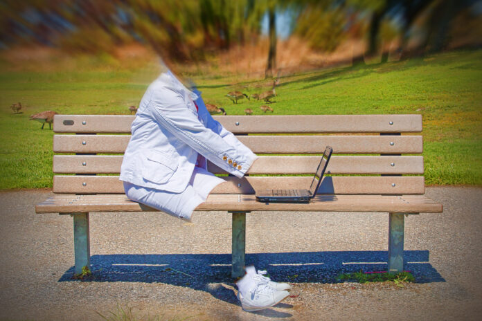 A woman sits on a park bench, typing on a computer. Her clothing and shoes are visible, but the woman within them is not visible.