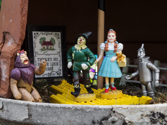 statues of Dorothy, Toto, the tin man, the scarecrow and the lion in front of a poster, which says there's no place like home