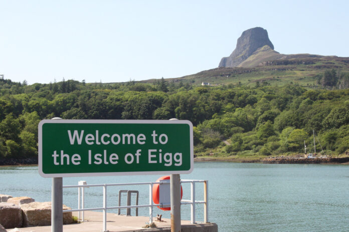 A sign on a pier reads 'welcome to the Isle of Eigg. A bald mountain rises across the water in the background