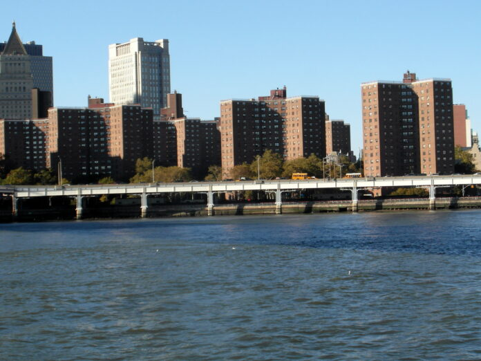 classic orange brick high rise public housing towers beside the East River in NYC.