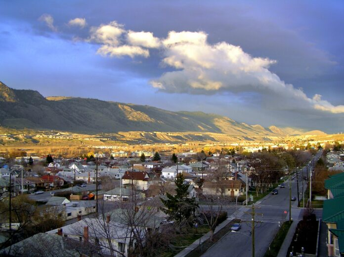 birds' eye view of downtown Kamloops in shadow with sun lighting the mountains in the background