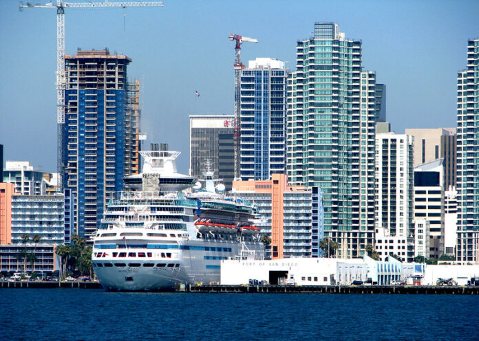 cruise ship in front of high rise buildings