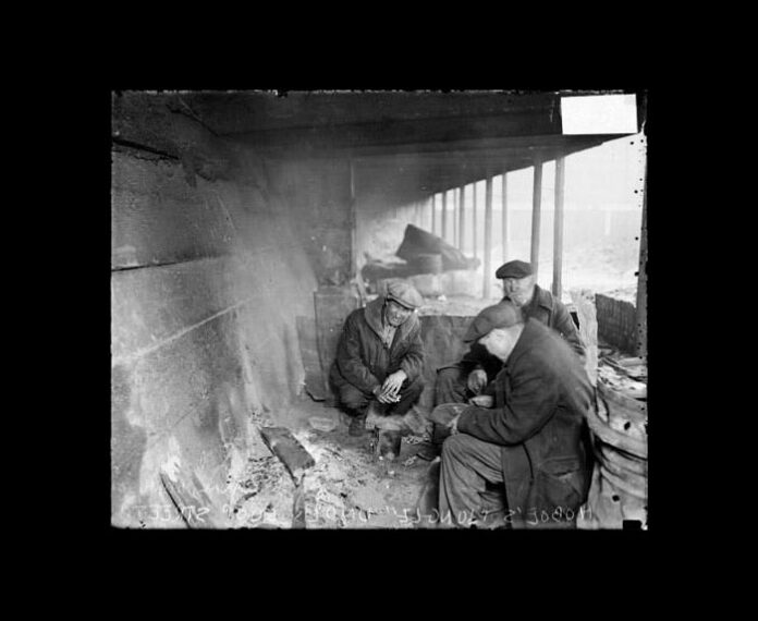 3 men in rough dress sitting beneath the Chicago elevated concrete supports