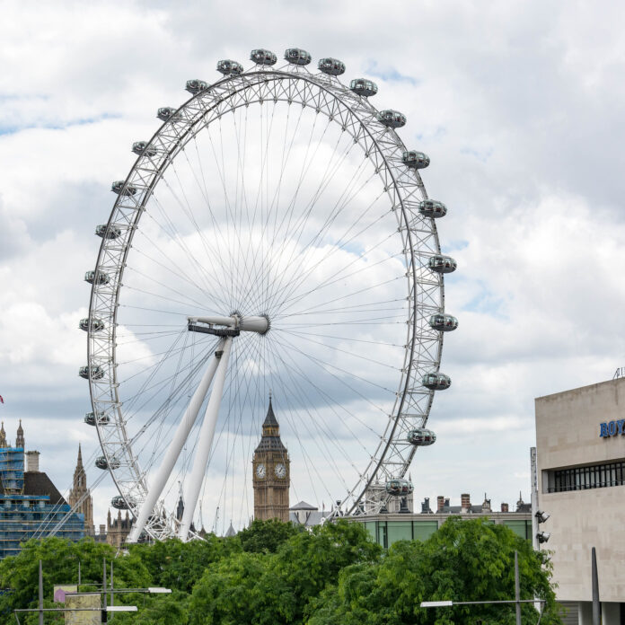 The huge ferris wheel that dominates portions of the london skyline frames big ben in the background
