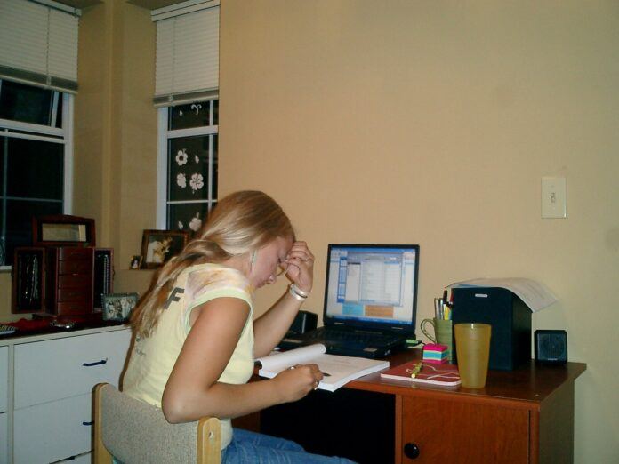 A young woman bent over a computer desk staring at a workbook