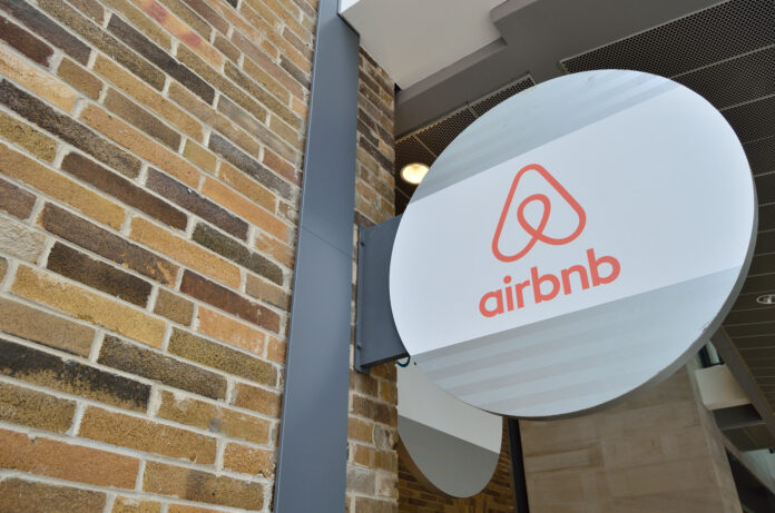 A sign fastened to a brick wall shows the symbol and name of airbnb