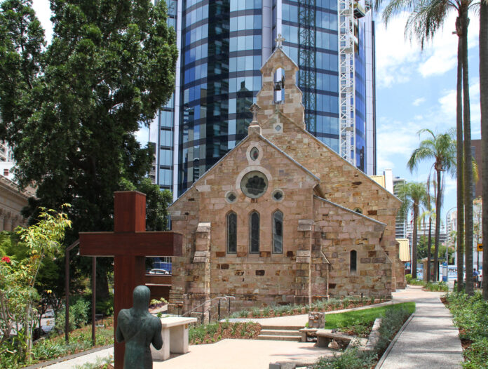 A modest stone church with a quiet courtyard, tall glass faces of high-rise buildings tower above it