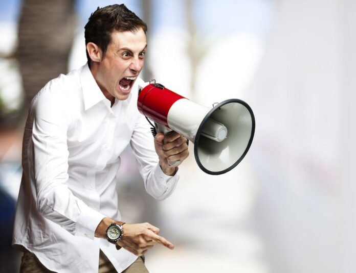 A manic looking man in a white shirt screaming through a megaphone