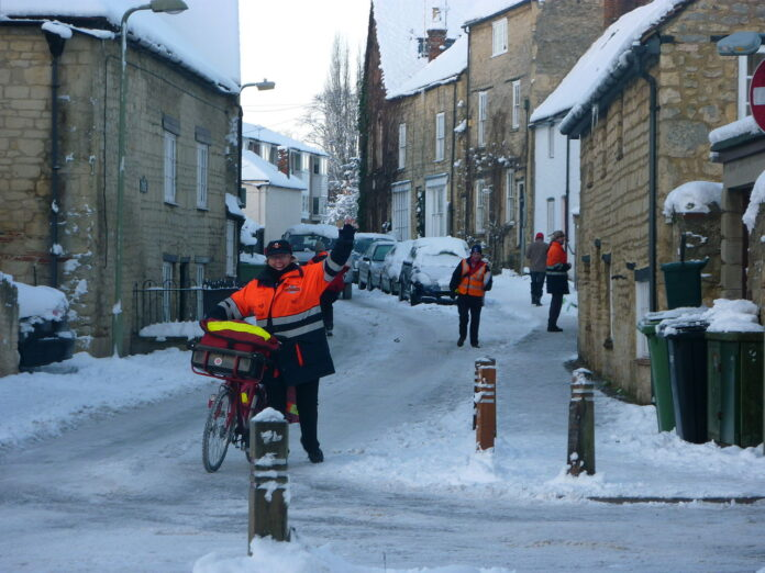 three letter carriers delivering mail on icy streets