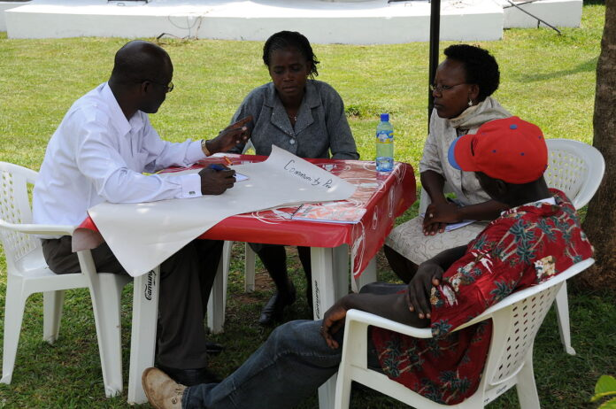 four adults in discussion seated around a table. one is taking notes