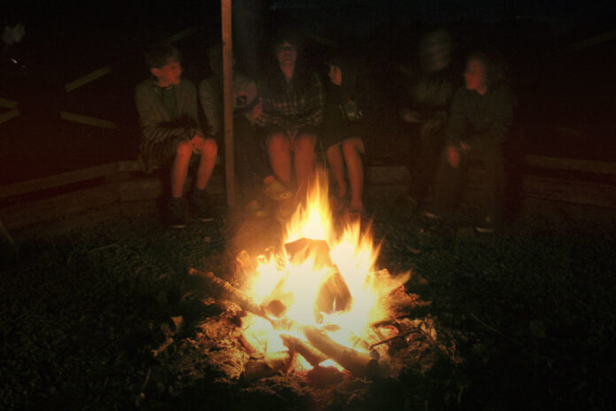 indistinct in the darkness, a family sits around a blazing campfire