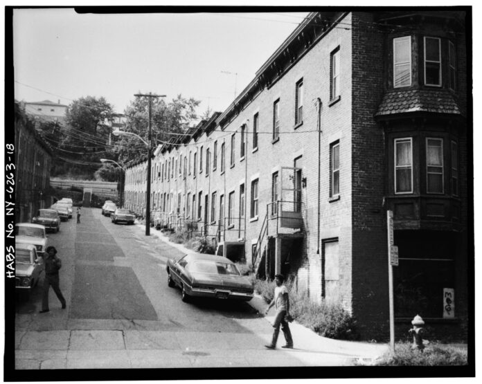 historic image of Moquette row, with pavement from house front to house front and no greenery at all