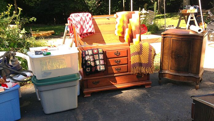 Furniture and other household necessities on the driveway in a yard sale.