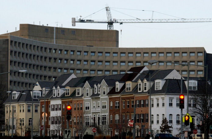 HUD headquarters rises behind row houses in Washington DC