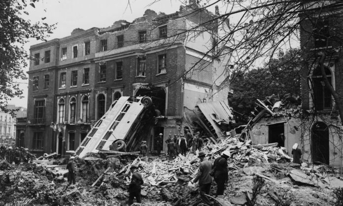 In a black and white photo a bomb-blasted London bus leans up against shattered houses