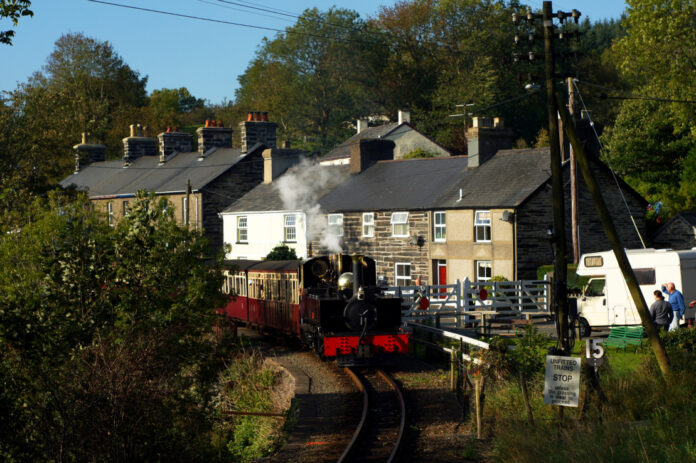 red tourist train passing homes in Gwynedd, Wales