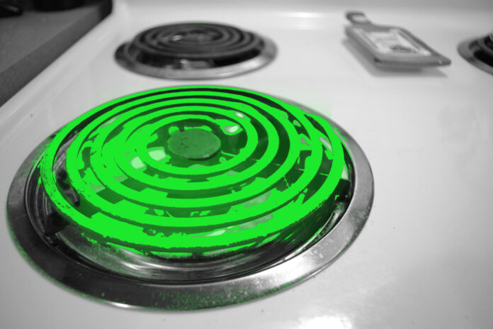 An electric burner glows green on a stove