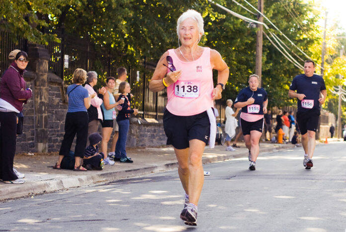 In shorts, T-shirt with a racing number on her chest, an older woman races ahead of some younger ones.