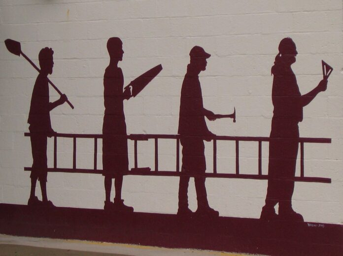 silhouette of labourers carrying a ladder, two of them clearly carpenters