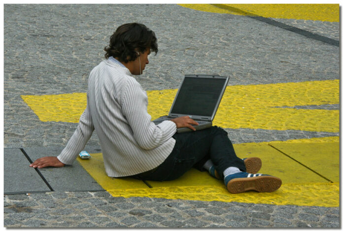 person using laptop sitting on pavement
