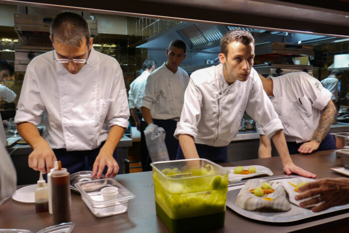 A crowded restaurant kitchen of white=clad workers prepares customer meals