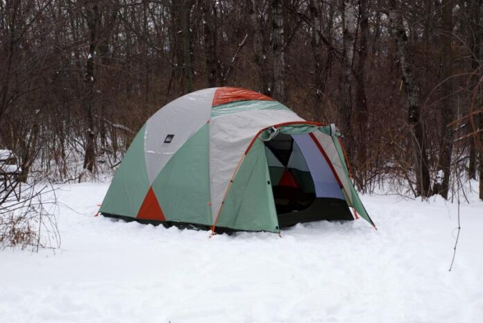 A multicoloured tent pitched on snow-covered ground