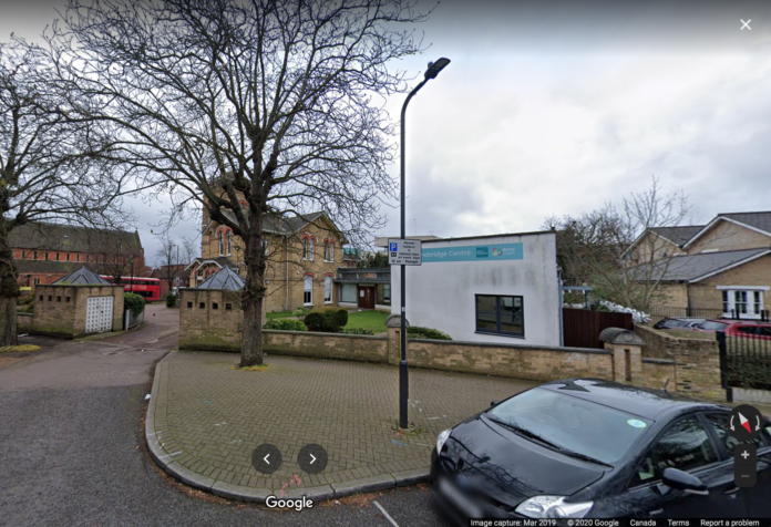 a google street view image of an old yellow building and a baby blue education centre add-on