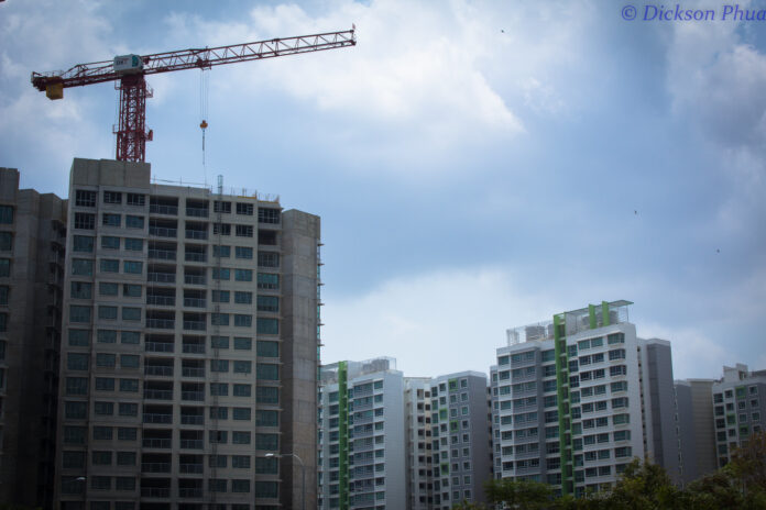 A crane rises above a new high-rise public housing building with a background of similar high rises