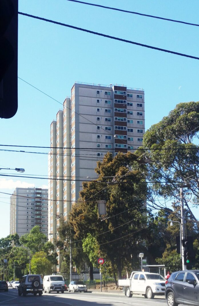 Two tall public housing tower blocks, built in grey concrete, stand on an inner-urban street which is lined with gum trees. Brunswick Street, Fitzroy, Melbourne, Victoria, Australia.
