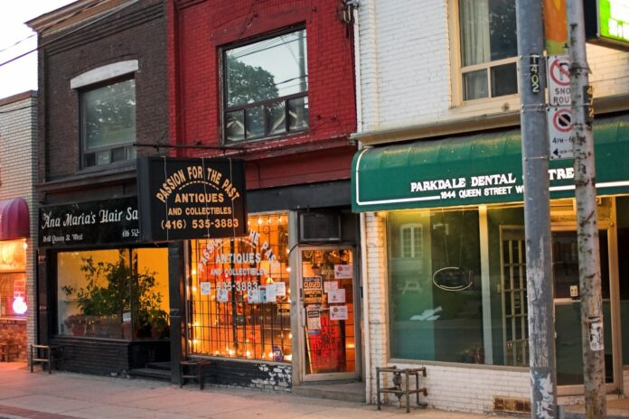 Evening storefronts lit by interior lighting on Queen Street, Parkdale, Toronto