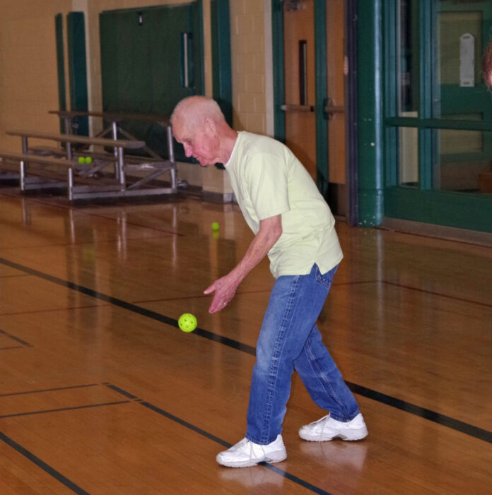 An older man bounces a green ball on a gym floor