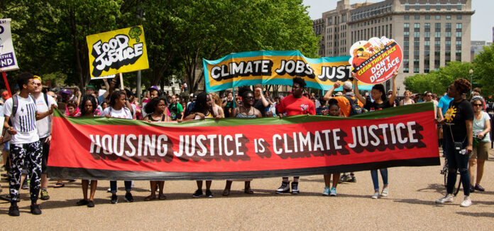 Protesters at a Washington D.C. rally hold a sign saying housing justice is climate justice
