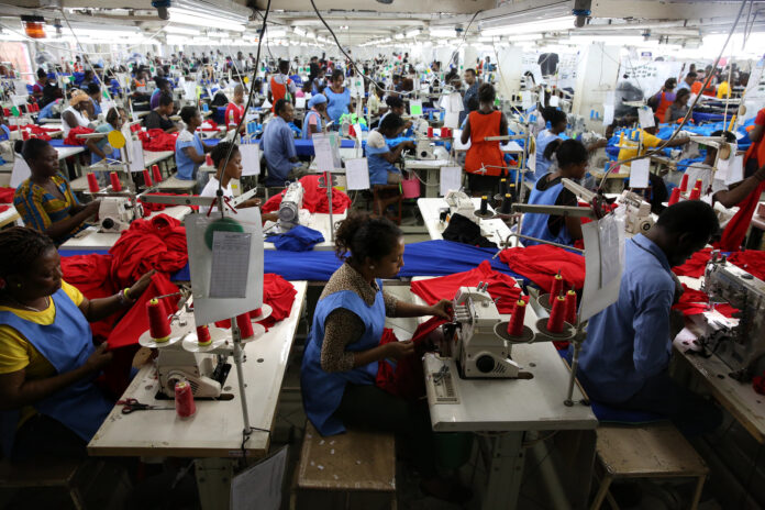 In a room that stretches on forever, garment workers toil at their machines.