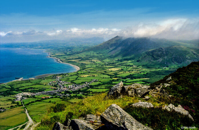A view from a mountain of a village far below on the North Wales coastal plain , with the sea in picture to the left