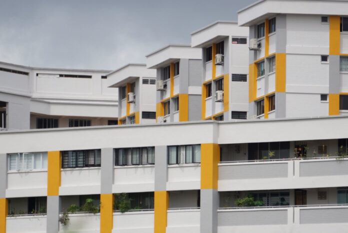 a small section of a public housing building in Singapore is a study in white contrasted with bright yellow