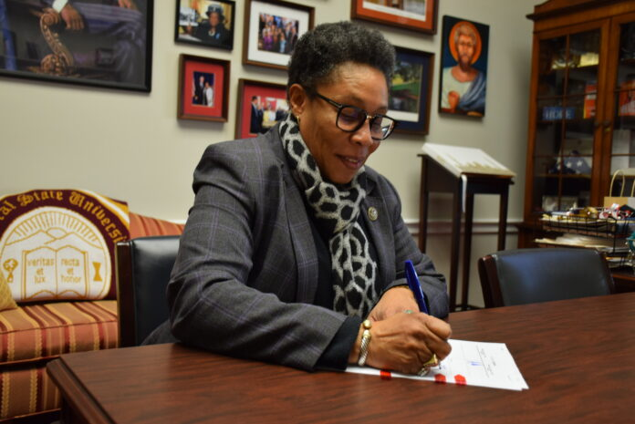 Marcia Fudge, a middle-aged Black woman, sits writing at a desk
