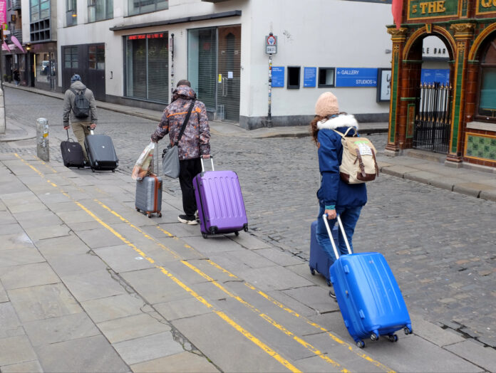 three people walking down an empty street with suitcases