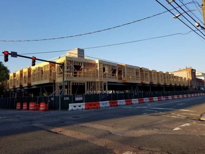 A block-long line of wooden framing picks out the shape of new apartments