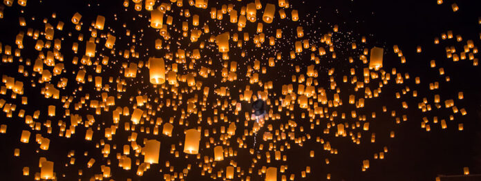 Thousands of orange candle-lit paper bags lift skyward in a Buddhist ceremony
