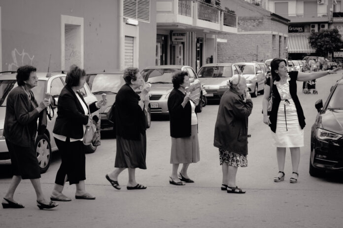 A queue of elderly white women array across a street, directed by a younger woman