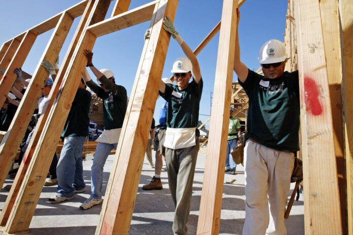 A team of volunteer builders in hard hats raise a wall frame to a vertical position.