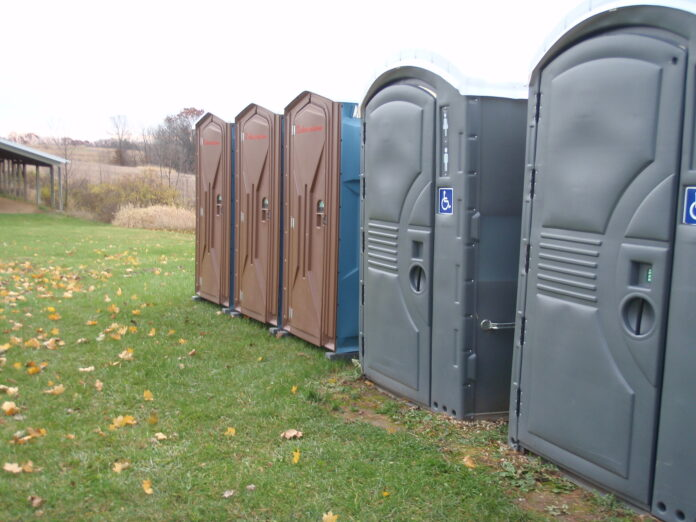 A row of 4 portable toilets stand in a field