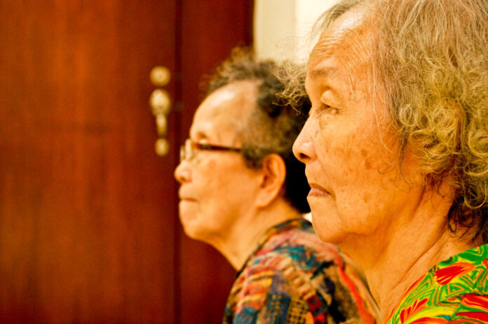 A closeup of 2 older women with oriental features watching a television that is not in picture